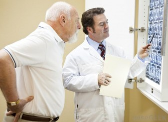 man-with-hands-on-back-looking-at-x-rays-with-doctor[1]